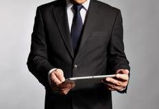 L'homme d'affaires tient un PC de table Photo stock
