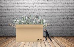 L'homme d'affaires tire une boîte énorme d'argent devant lui sur le fond du mur de briques et du plancher en bois photos stock