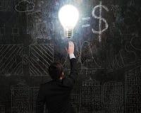 L'homme d'affaires touchant brillamment l'ampoule a illuminé le griffonnage foncé Photographie stock