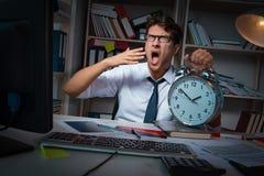 L'homme d'affaires d'homme travaillant des heures en retard dans le bureau Images libres de droits