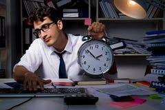 L'homme d'affaires d'homme travaillant des heures en retard dans le bureau Photo stock