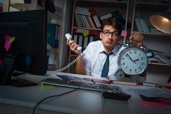 L'homme d'affaires d'homme travaillant des heures en retard dans le bureau Photos stock