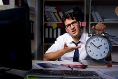 L'homme d'affaires d'homme travaillant des heures en retard dans le bureau Photographie stock