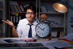 L'homme d'affaires d'homme travaillant des heures en retard dans le bureau Images stock