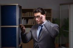 L'homme d'affaires travaillant des heures en retard dans le bureau Image libre de droits