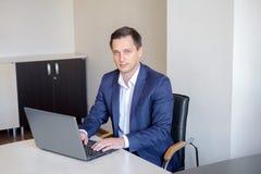 L'homme d'affaires travaille avec l'ordinateur portable dans le bureau regarde l'appareil-photo image stock