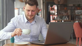 L'homme d'affaires travaille sur l'ordinateur portable au café