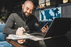 L'homme d'affaires travaille sur l'ordinateur portable, faisant des notes dans le document, parle dans des ?couteurs au t?l?phone image stock