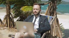 L'homme d'affaires travaille sur son ordinateur portable sur la plage tropicale clips vidéos