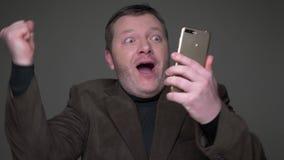 L'homme d'affaires d'une cinquantaine d'années de brune dans le costume fonctionnant avec le téléphone obtient extrêmement amusé  banque de vidéos
