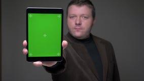 L'homme d'affaires d'une cinquantaine d'années de brune dans le costume montre l'écran vert du comprimé pensivement sur le fond g banque de vidéos