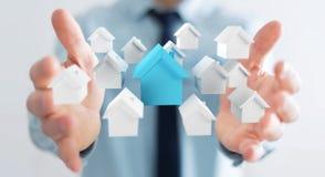 L'homme d'affaires utilisant 3D a rendu de petites maisons blanches et bleues Photographie stock