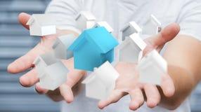 L'homme d'affaires utilisant 3D a rendu de petites maisons blanches et bleues Photographie stock libre de droits