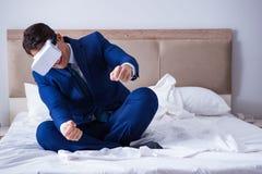 L'homme d'affaires utilisant un casque de réalité virtuelle dans la chambre à coucher Image stock