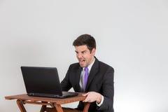 L'homme d'affaires yalling à un ordinateur portable Photo stock