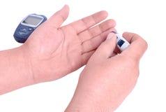 L'homme d'analyse de sang remet vérifier le taux du sucre dans le sang par le glucose distribuent Photographie stock