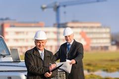 L'homme d'architecte effectuent des notes sur le chantier de construction Photographie stock