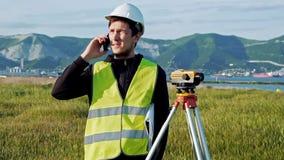 L'homme d'arpenteur dans les vêtements et le casque de travail verts ajuste l'équipement, produit des calculs et écrit au carnet  clips vidéos