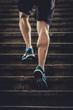 L'homme d'athlète avec la jambe forte muscles l'escalier urbain de ville de formation et de fonctionnement dans la forme physique Photo stock