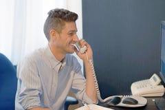 L'homme d'employé de bureau répond à l'appel photos libres de droits