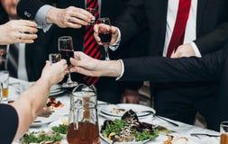 L'homme d'entreprise constituée en société grillant à la table de dîner remet des clos image stock