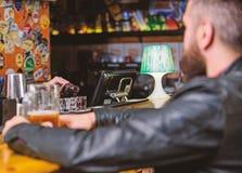 L'homme d?pensent des loisirs dans le bar fonc? L'homme s'asseyent au compteur de barre dans le bar Mode de vie de week-end Alcoo photo libre de droits