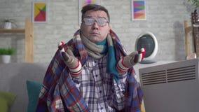 L'homme d'une cinquantaine d'années congelé s'est enveloppé dans une couverture est chauffé à côté du radiateur électrique et des banque de vidéos