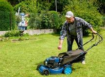 L'homme d'une cinquantaine d'années déplace la pelouse photographie stock libre de droits