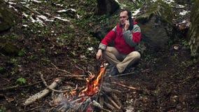 L'homme d'une cinquantaine d'ann?es s'assied par le feu dans la for?t banque de vidéos