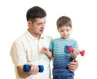 L'homme d'une cinquantaine d'années et l'enfant s'exercent avec l'haltère Images stock