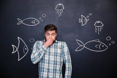 L'homme d'une manière amusante a fermé le nez et la position au-dessus du tableau avec des poissons Image libre de droits