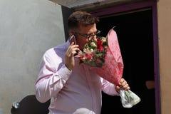 L'homme dans l'amour avec un grand bouquet des fleurs, parle avec son aimé au téléphone photos stock