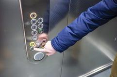 L'homme dans l'ascenseur presse son doigt sur le bouton pour fermer la porte photo stock