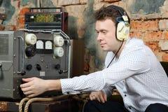 L'homme dans des écouteurs configure la source d'énergie au récepteur radioélectrique Photographie stock