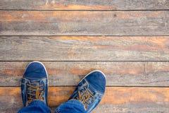 L'homme dans des espadrilles de mode se tient sur un vieux plancher en bois Copiez les stations thermales Photos stock