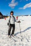 L'homme dans des lunettes de ski-costume, de casque et de ski skie dans un ski-resor Photos stock