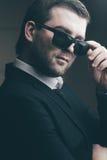 L'homme dans des lunettes de soleil a abaissé dans la chambre noire images stock