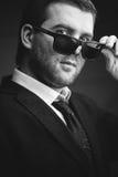 L'homme dans des lunettes de soleil a abaissé dans la chambre noire photo stock