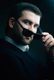 L'homme dans des lunettes de soleil a abaissé dans la chambre noire photographie stock libre de droits