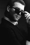 L'homme dans des lunettes de soleil a abaissé dans la chambre noire image libre de droits