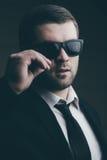 L'homme dans des lunettes de soleil a abaissé dans la chambre noire photo libre de droits