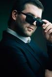 L'homme dans des lunettes de soleil a abaissé dans la chambre noire image stock