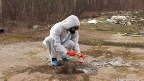 L'homme dans des masques de costume et de gaz de bio-risque prend l'eau et la terre pour l'analyse clips vidéos