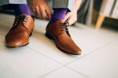 L'homme dans des mous gris et une robe pourpre cogne les chaussures brunes avec photographie stock