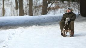 L'homme dans l'horaire d'hiver sledding Neige partout banque de vidéos