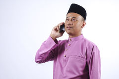 L'homme dans l'habillement traditionnel avec le smartphone célèbrent Eid Fitr Photos libres de droits