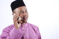 L'homme dans l'habillement traditionnel avec le smartphone célèbrent Eid Fitr Image libre de droits