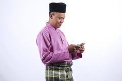 L'homme dans l'habillement traditionnel gai avec le paquet d'argent pendant célèbrent Eid Fitr Photos libres de droits