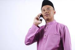 L'homme dans l'habillement traditionnel gai avec le paquet d'argent pendant célèbrent Eid Fitr Image libre de droits