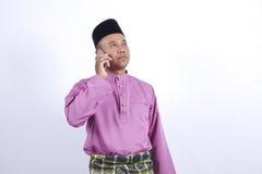 L'homme dans l'habillement traditionnel, se tenant célèbrent Eid Fitr Photo libre de droits